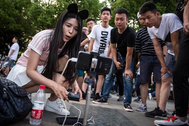 Một nữ Youtuber sử dụng điện thoại thông minh để phát trực tiếp lễ hội Douyu trên mạng. Ảnh: Wang HE/Getty Images.